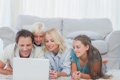 Belle famille utilisant un ordinateur portable se trouvant sur un tapis Photographie stock libre de droits
