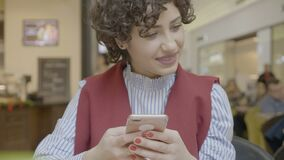 Belle femelle avec les cheveux bouclés courts souriant et à l'aide de son smartphone tout en sirotant de la tasse dans le café au clips vidéos