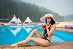 Belle femelle dans un chapeau et un bikini noir se reposant à côté de la piscine, du cocktail potable et regardant à l'appareil-p Image stock
