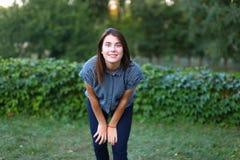 Belle femelle regardant in camera et dupant autour en parc dessus Photographie stock libre de droits