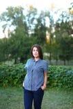 Belle femelle regardant in camera, sourire mignon en parc sur le backgr Images stock