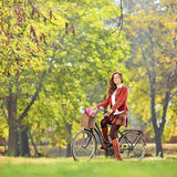 Belle femelle sur une bicyclette en parc regardant l'appareil-photo Photo libre de droits