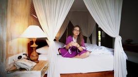 Belle femme à l'aide du téléphone dans le lit contrôlant la maison reliée futée avec l'appli mobile clips vidéos