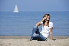 Belle femme à la plage avec un téléphone portable Images libres de droits