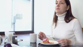 Belle femme à une table de café mangeant un gâteau et buvant du café banque de vidéos