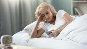 Belle femme âgée se situant dans le lit, causant dans les réseaux sociaux sur le smartphone photographie stock
