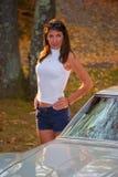 Belle femme éclairée à contre-jour à côté de la pastenague de Corvette Image libre de droits