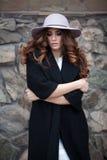 Belle femme élégante dans l'ove noir à la mode élégant de manteau et de chapeau Photos libres de droits