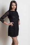 Belle femme élégante sexy avec les longs cheveux, maquillage lumineux de soirée dans une robe de soirée noire dans le studio sur  Photo stock