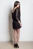 Belle femme élégante sexy avec les longs cheveux, maquillage lumineux de soirée dans une robe de soirée noire dans le studio sur  Photographie stock