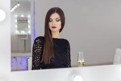 Belle femme élégante sexy avec les longs cheveux, maquillage lumineux de soirée dans une robe de soirée noire dans le studio sur  image libre de droits