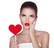 Belle femme étonnée avec le maquillage lumineux de charme tenant le rouge Photographie stock