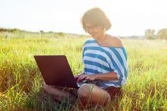 Belle femme adulte s'asseyant sur l'herbe et travaillant au Photo libre de droits
