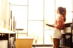 Belle femme affichant un livre dans une bibliothèque Photographie stock libre de droits