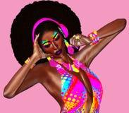 Belle femme africaine dans un équipement coloré de rubans, écouteurs de port photos libres de droits