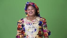 Belle femme africaine de poids excessif portant l'habillement traditionnel sur le fond vert banque de vidéos