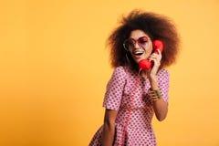 Belle femme africaine de sourire dans la robe posant avec le rétro téléphone images stock