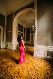 Belle femme africaine sexy dans la robe rouge posant aux appartements de luxe Photographie stock