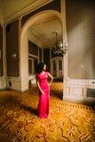 Belle femme africaine sexy dans la robe rouge posant aux appartements de luxe Image stock