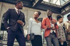 Belle femme Afro dans la jupe de mode et blose écoutant ses collègues photos libres de droits