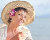 Belle femme agée dans un chapeau avec un cocktail à disposition Été Image stock