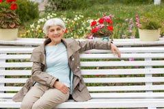 Belle femme agée mignonne s'asseyant sur un banc de parc avec des fleurs Image stock