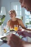 Belle femme agissant l'un sur l'autre tout en ayant le repas avec des amis Photos libres de droits