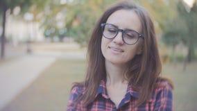 Belle femme 40 années avec des verres regardant l'appareil-photo et le sourire banque de vidéos