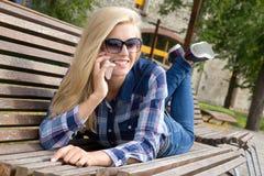 Belle femme appelant par le téléphone et se trouvant sur le banc en parc Photographie stock