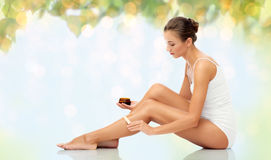 Belle femme appliquant la cire dépilatoire à sa jambe image stock