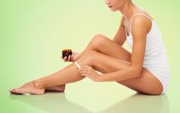 Belle femme appliquant la cire dépilatoire à sa jambe images stock