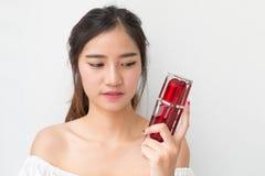 Belle femme appliquant la crème cosmétique, solated avec couper la PA Photographie stock