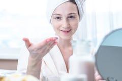 Belle femme appliquant la crème des cosmétiques naturels sur le visage hydratant la peau Hygiène et entretenir la peau à la maiso image stock