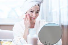 Belle femme appliquant la crème des cosmétiques naturels sur le visage hydratant la peau Hygiène et entretenir la peau à la maiso photographie stock libre de droits