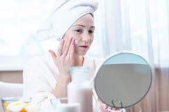 Belle femme appliquant la crème des cosmétiques naturels sur le visage hydratant la peau Hygiène et entretenir la peau à la maiso photo stock