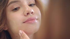 Belle femme appliquant la crème pour peler tandis que maquillage de visage au miroir dans la salle de bains clips vidéos
