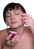 Belle femme appliquant la crème sur le visage Photo libre de droits