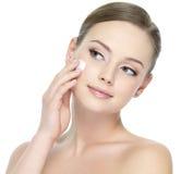 Belle femme appliquant la crème sur le visage Image stock