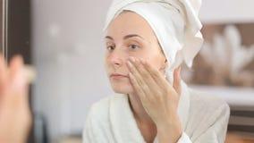 Belle femme appliquant la lotion de soins de la peau au visage entretenant la peau banque de vidéos