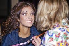 Belle femme appliquant la poudre sur la joue avec la brosse Photo stock