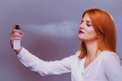 Belle femme appliquant le jet d'hydration d'arrangement de maquillage sur le visage Image libre de droits