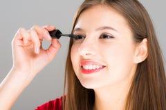 Belle femme appliquant le mascara sur ses cils photographie stock libre de droits