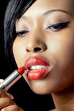 Belle femme appliquant le rouge à lievres Photos stock
