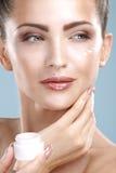 Belle femme appliquant le traitement crème sur son visage parfait photos libres de droits