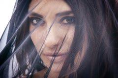 Belle femme arabe musulmane dans le paranja sur l'obscurité Images stock