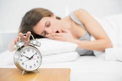 Belle femme arrêtant le réveil se trouvant sur son lit Photo stock