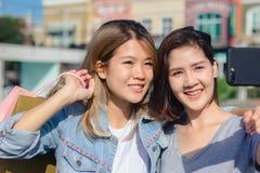 Belle femme asiatique attirante à l'aide d'un smartphone tandis que shoppi Photo libre de droits