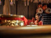 Belle femme asiatique avec l'habillement de tradition tenant le cylindre en bambou des bâtons de Chi de Chi ou du Chien Tung, Cou photographie stock