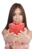 Belle femme asiatique avec le foyer rouge de boîte-cadeau sur la boîte Image libre de droits