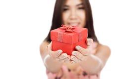 Belle femme asiatique avec le foyer rouge de boîte-cadeau sur la boîte Photographie stock libre de droits